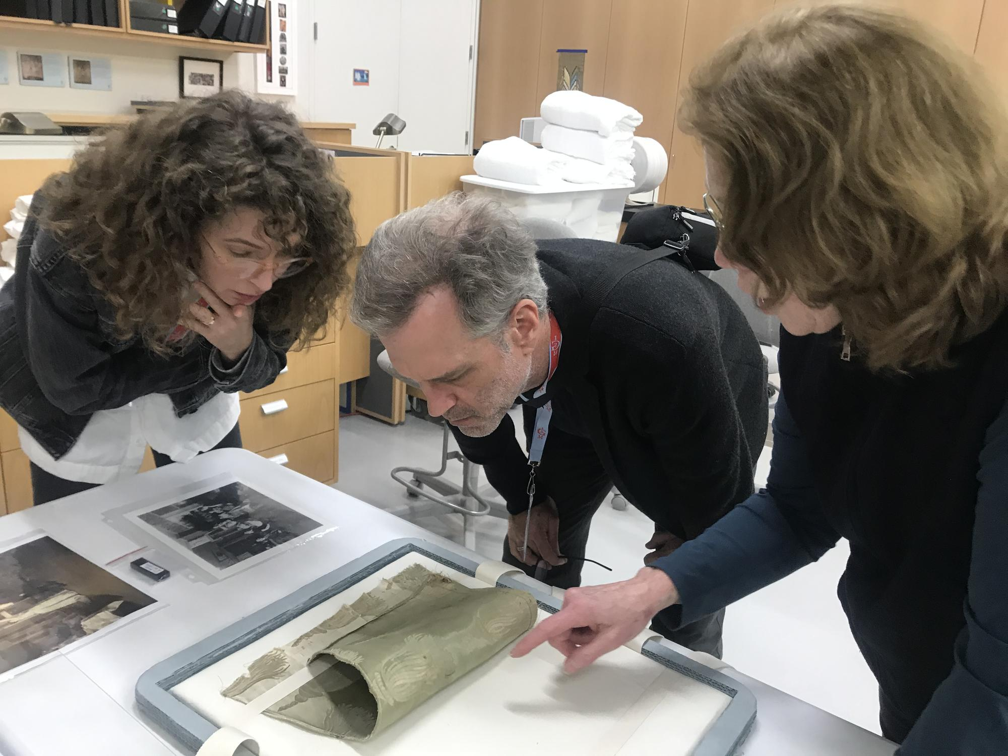 Mary Reid Kelley and Patrick Kelley look at an original fragment of the dress Gardner cut apart and installed under Titian's Europa, 2019