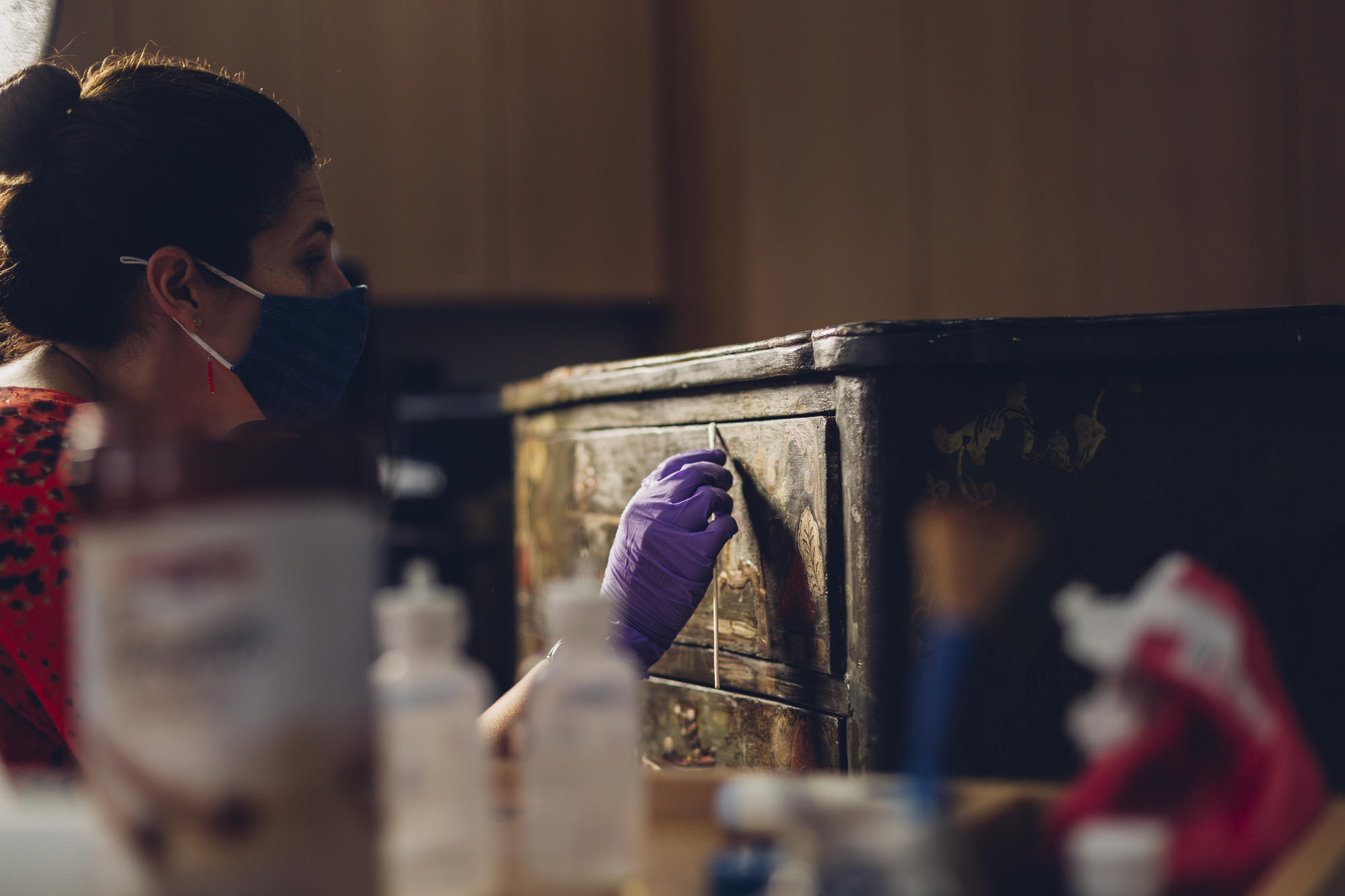 Jess Chloros removes discolored varnish from an object