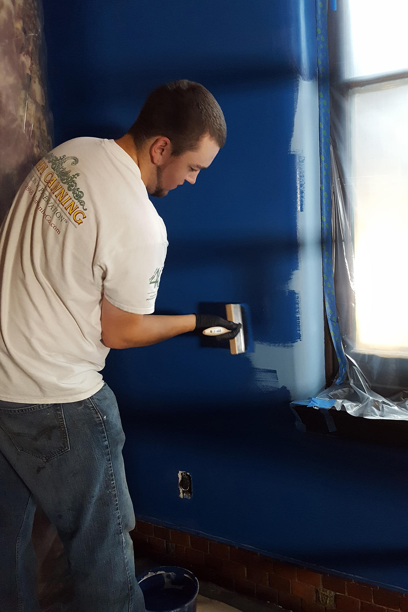 A man painting the walls blue