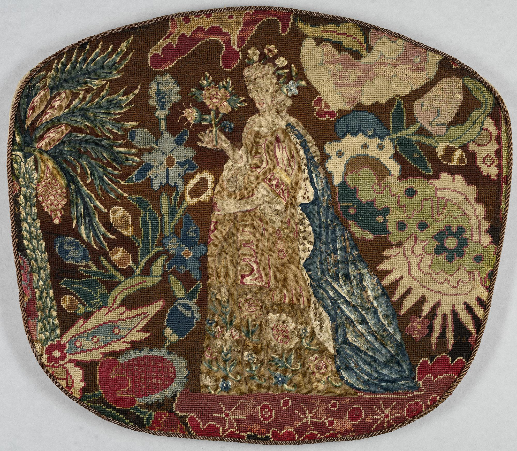 A sewn piece with a woman in a dress surrounded by plants