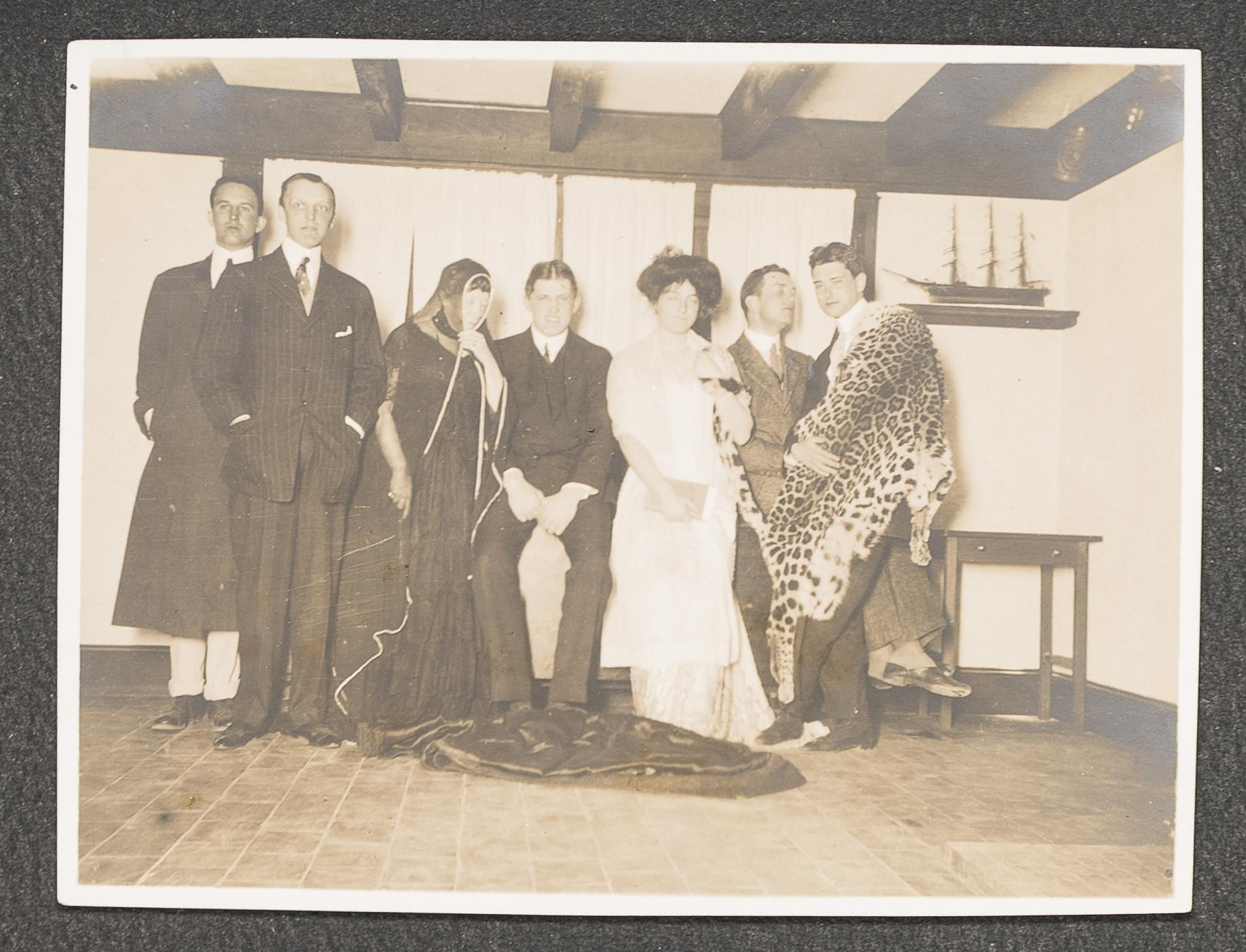 Black and white photo of 7 people, one wearing a tiger pelt