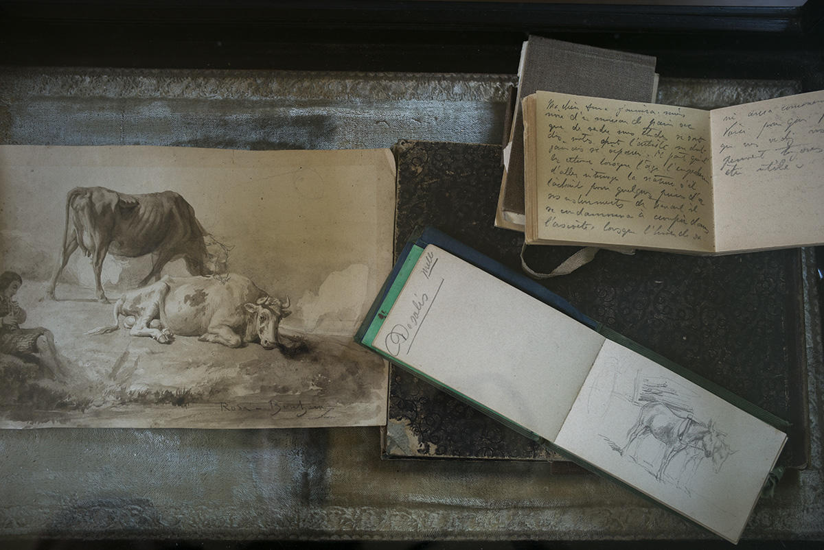 Two sketches and a journal on a dark table