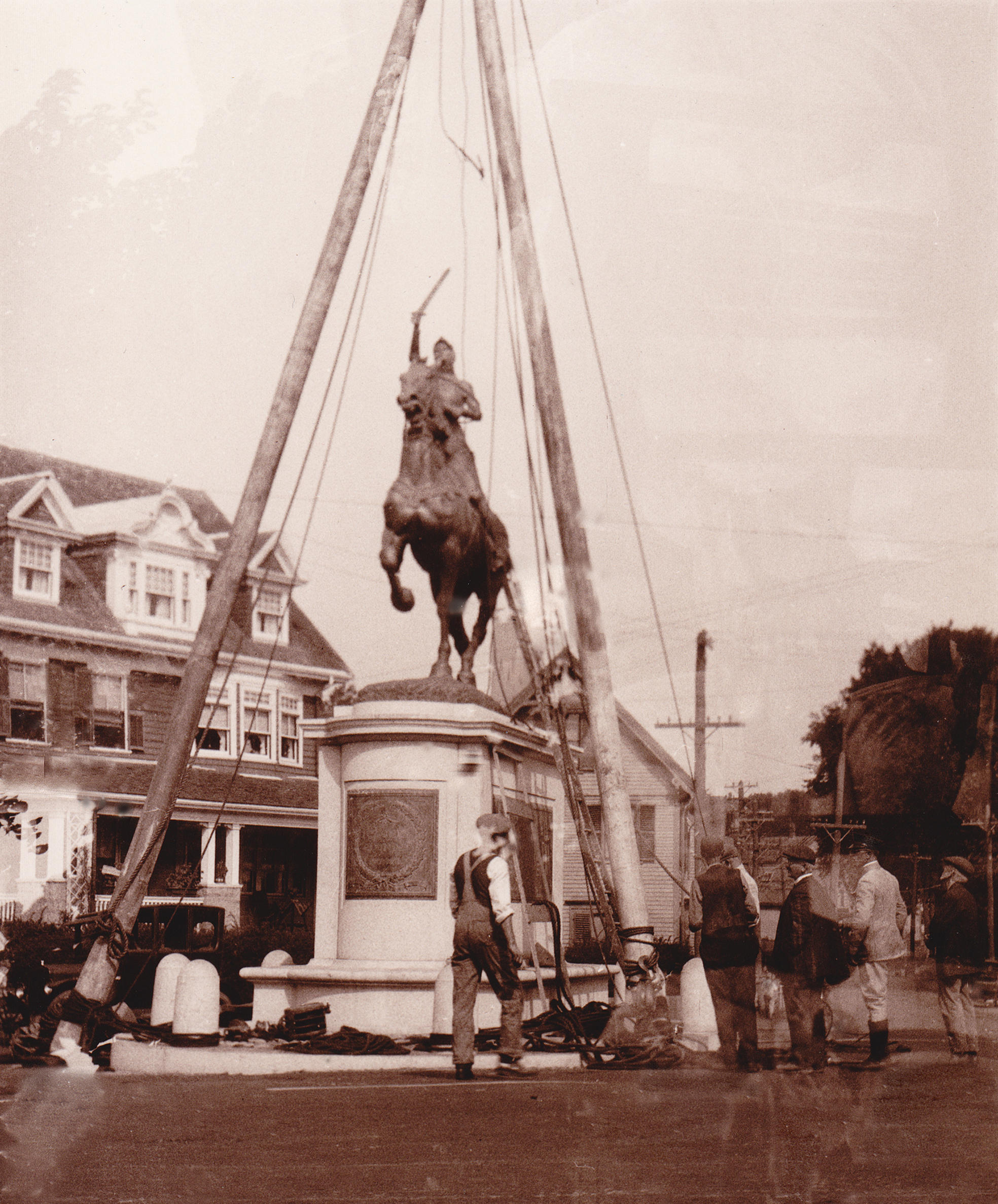 A photograph of builders placing a statue on a pedestal