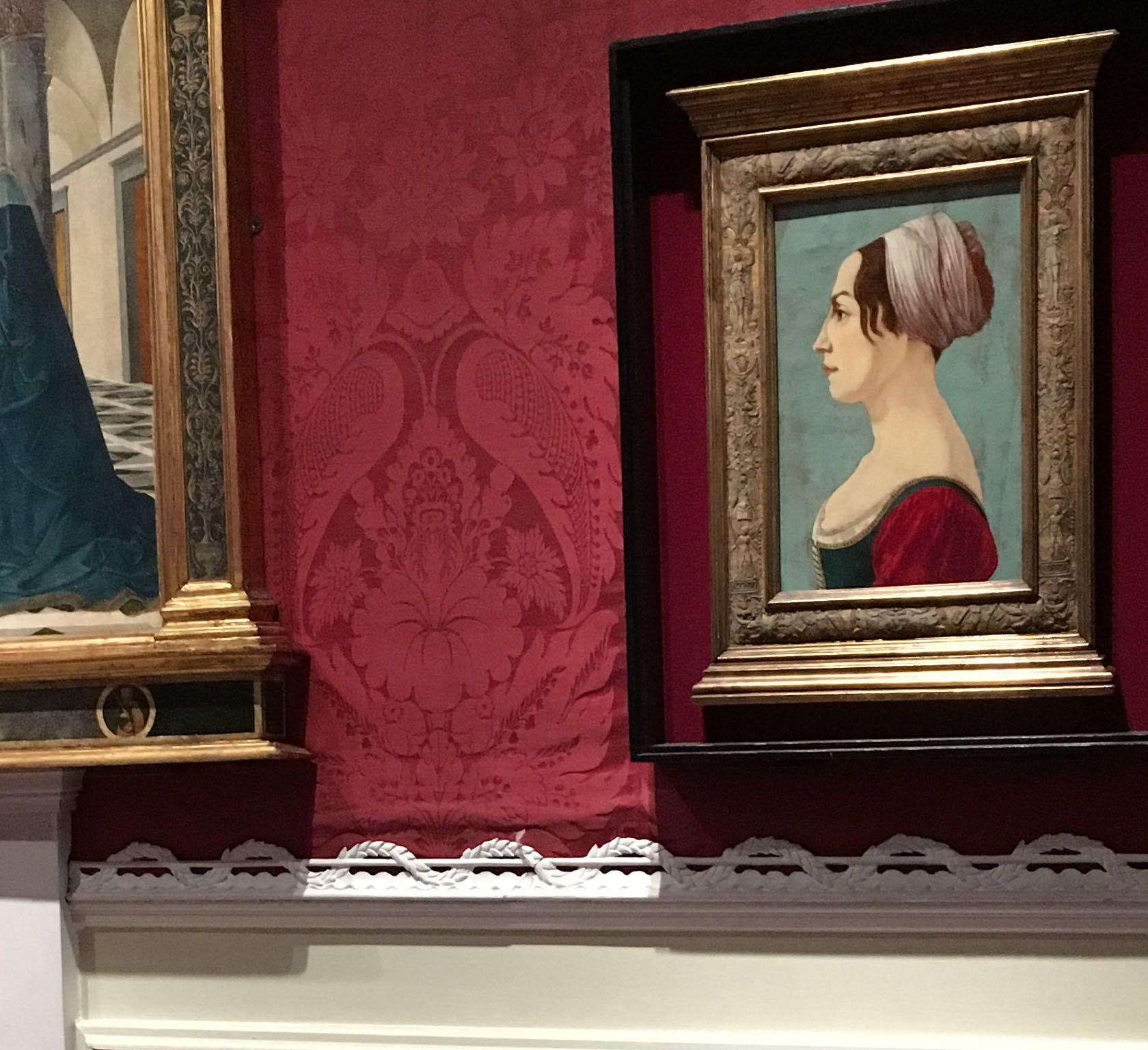 Paintings on a red wall with silk drooping.