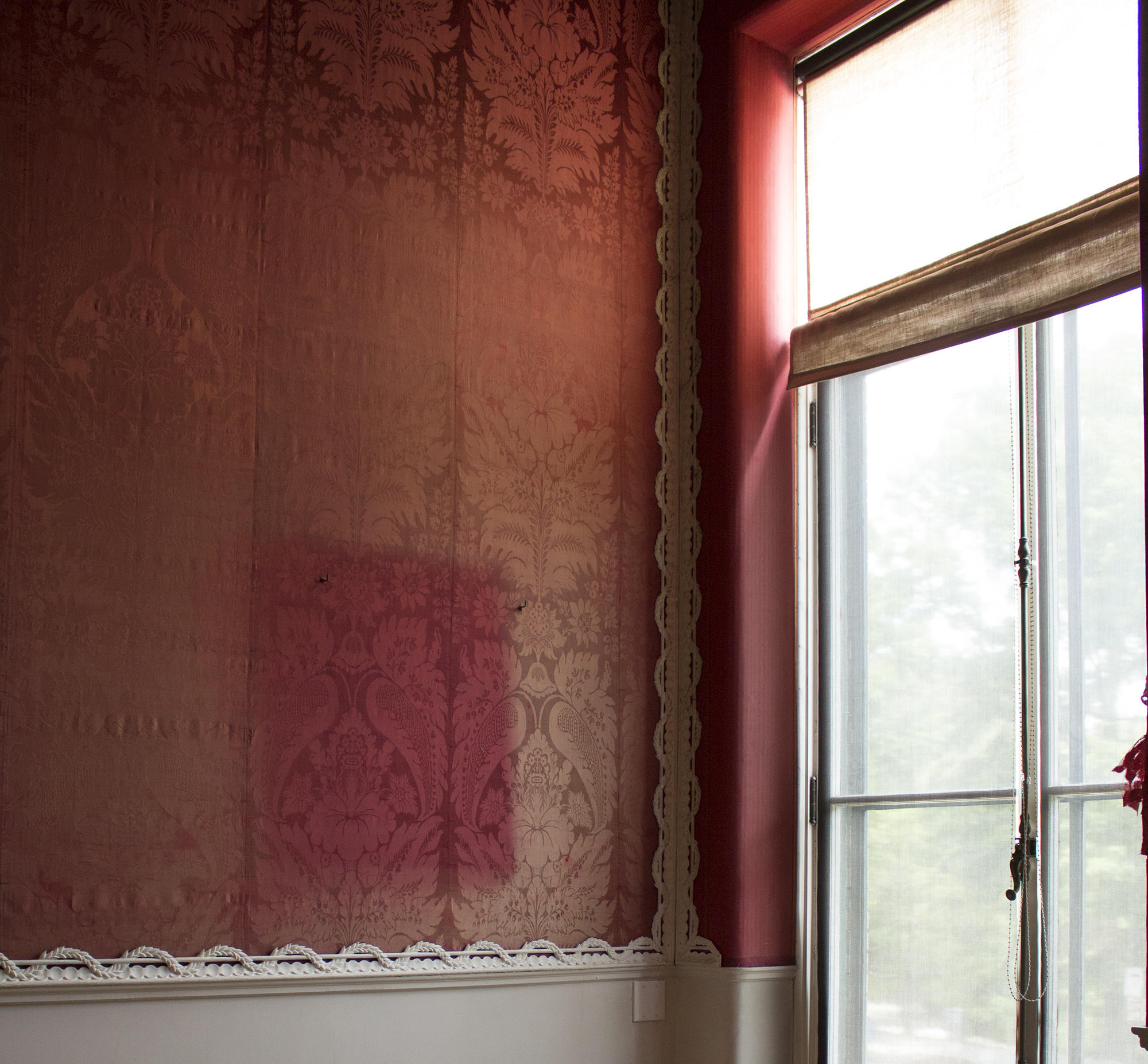 Red silk walls with noticeable light discoloration.