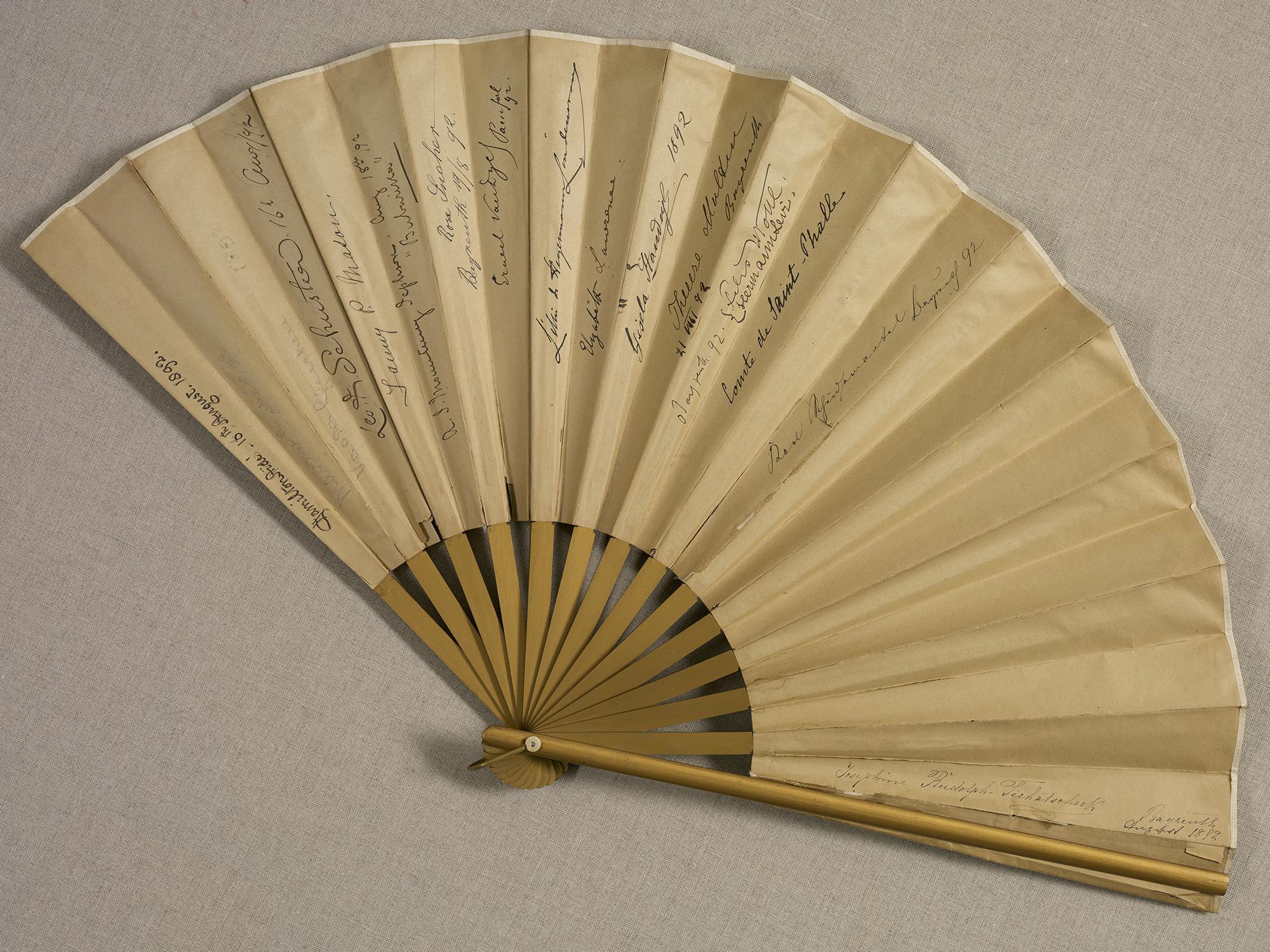 A tan folding fan with some writing.