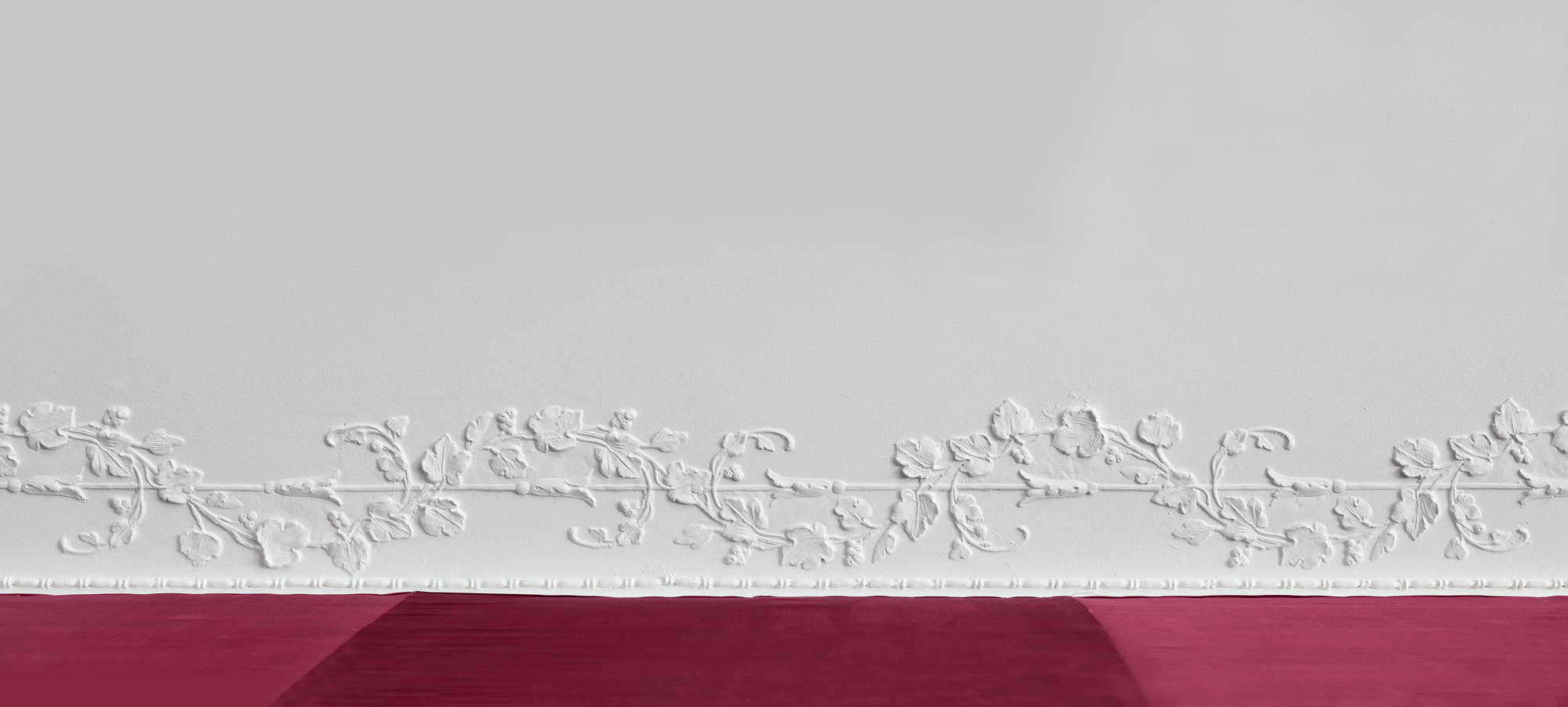 Molding on a white wall with a red banner underneath.