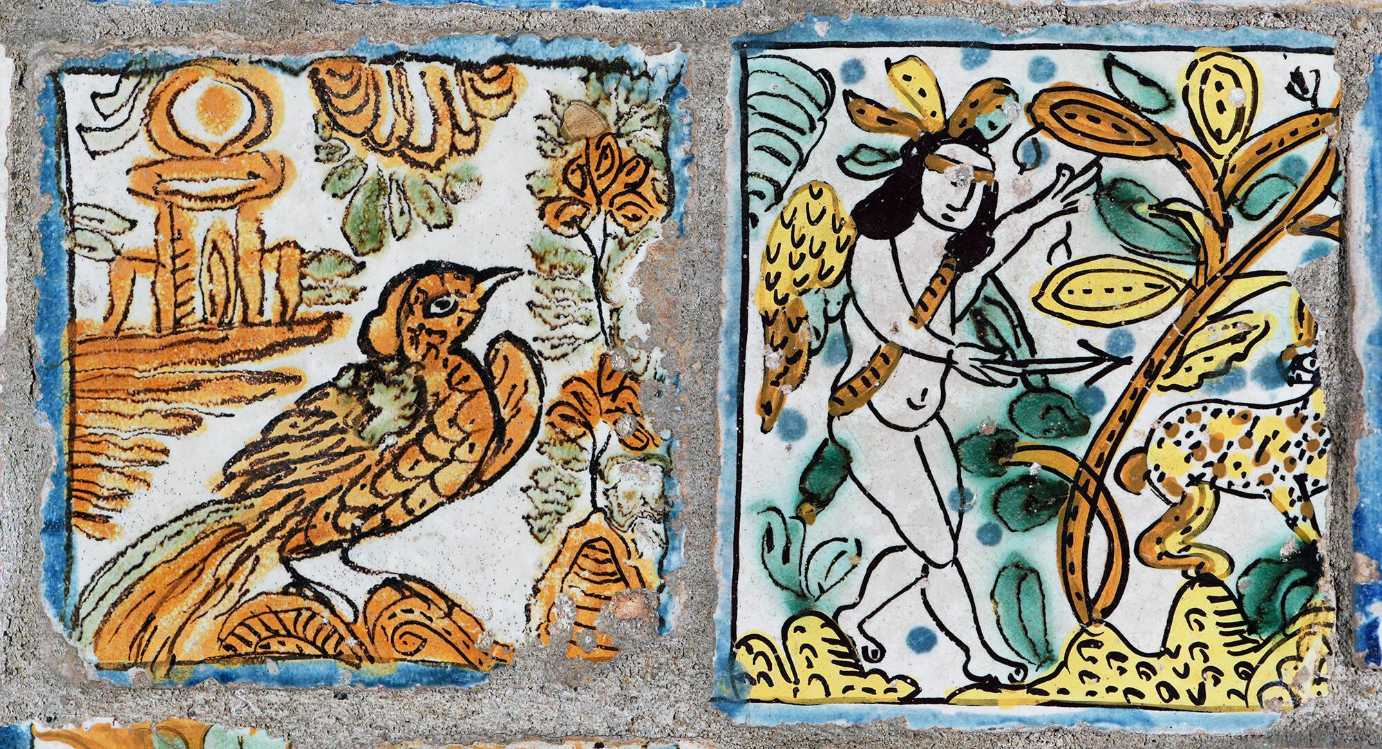 A tile with an orange bird painted on the left and a tile with a naked person painted on the right.