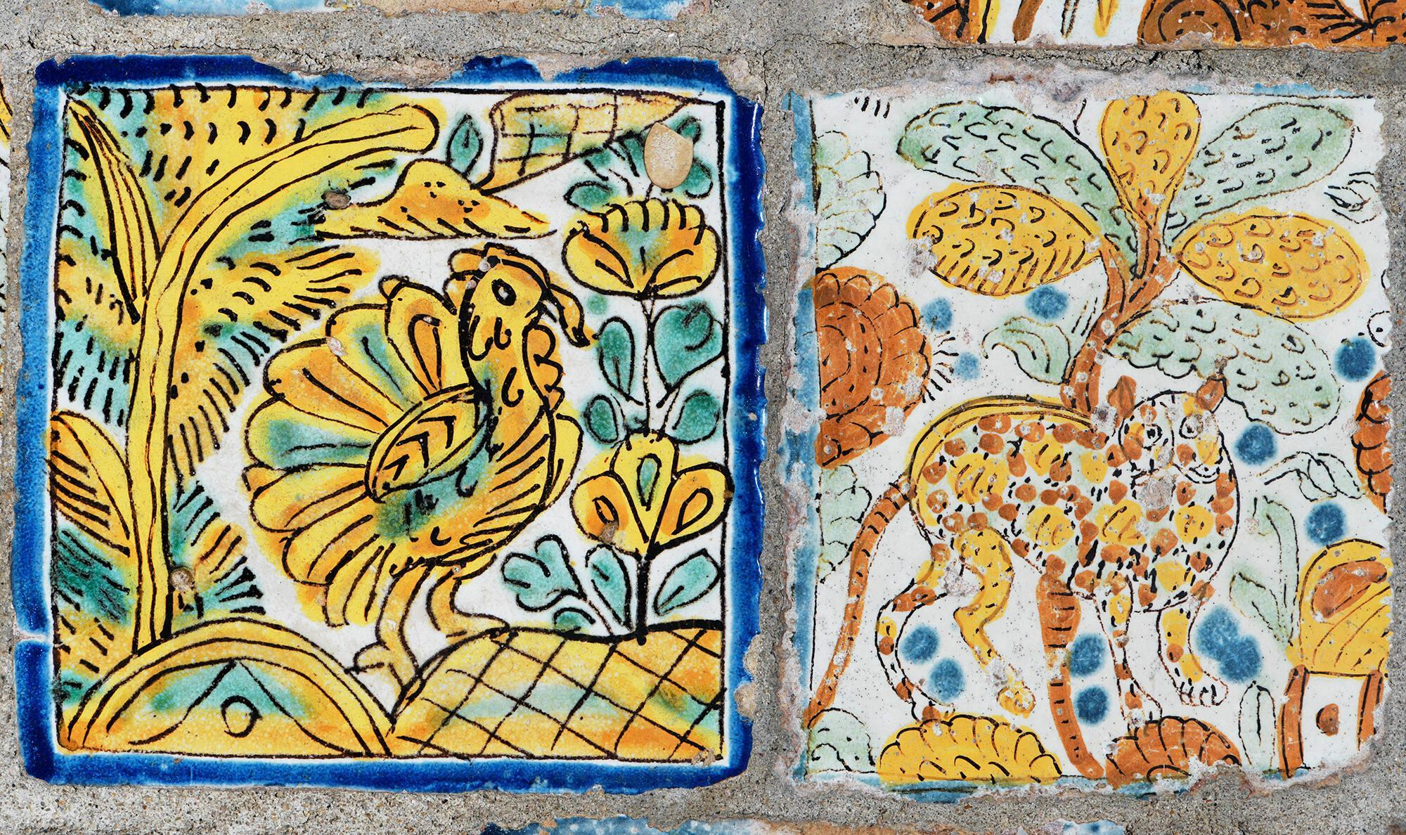 A tile with a bird painted on it on the left and a tile with a big cat painted on it on the right.