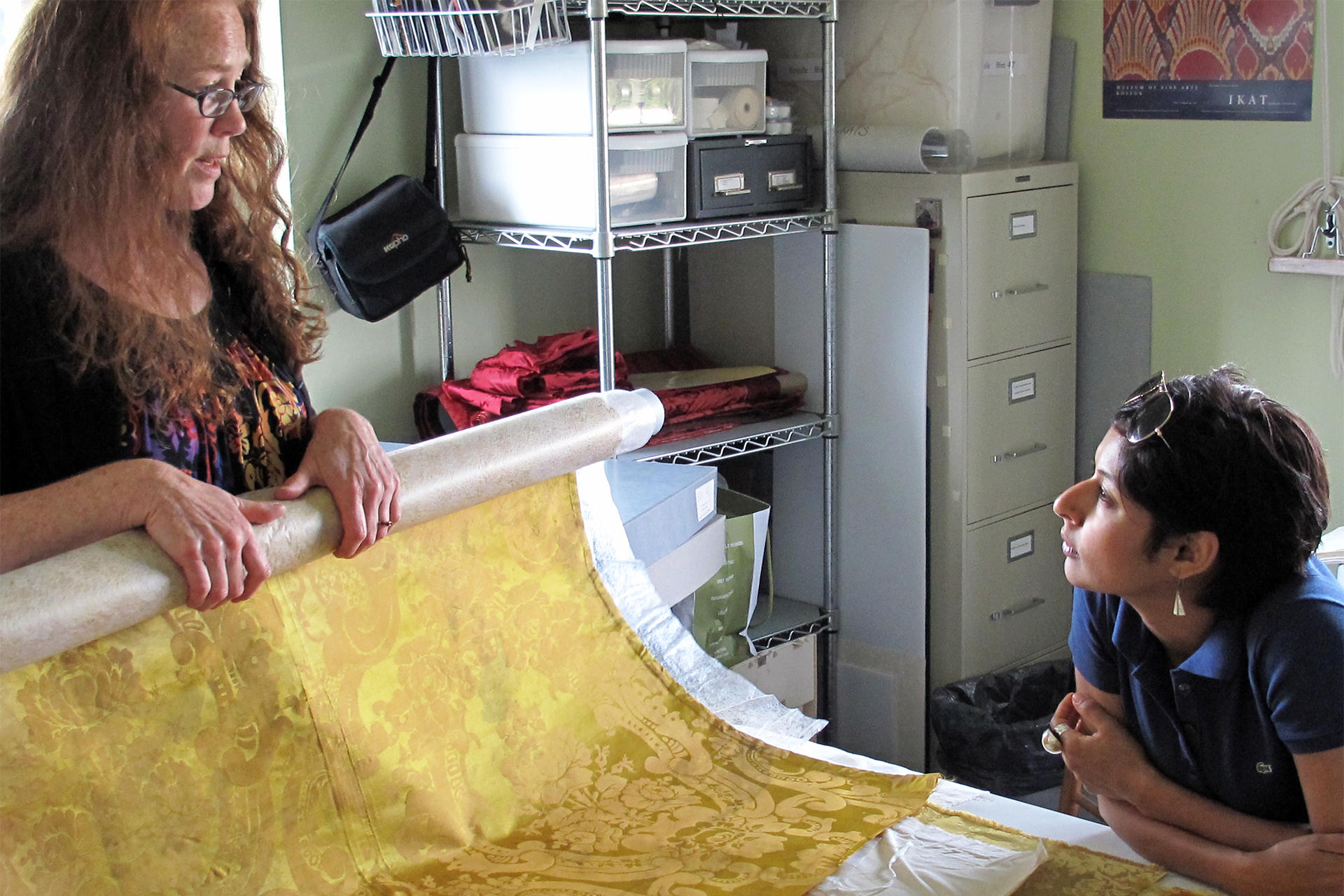 Artist-in-Residence Hamra Abbas looking at textiles in the conservation lab.