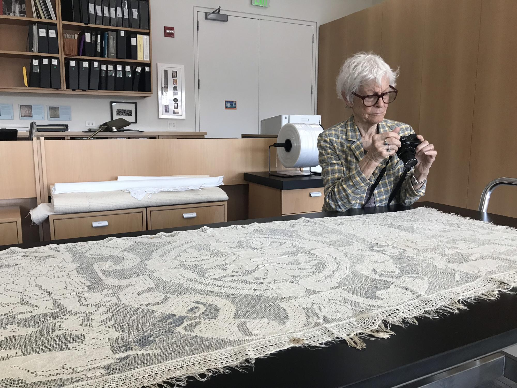 Joan Jonas photographing lace in the Textile Conservation Lab, 2018.