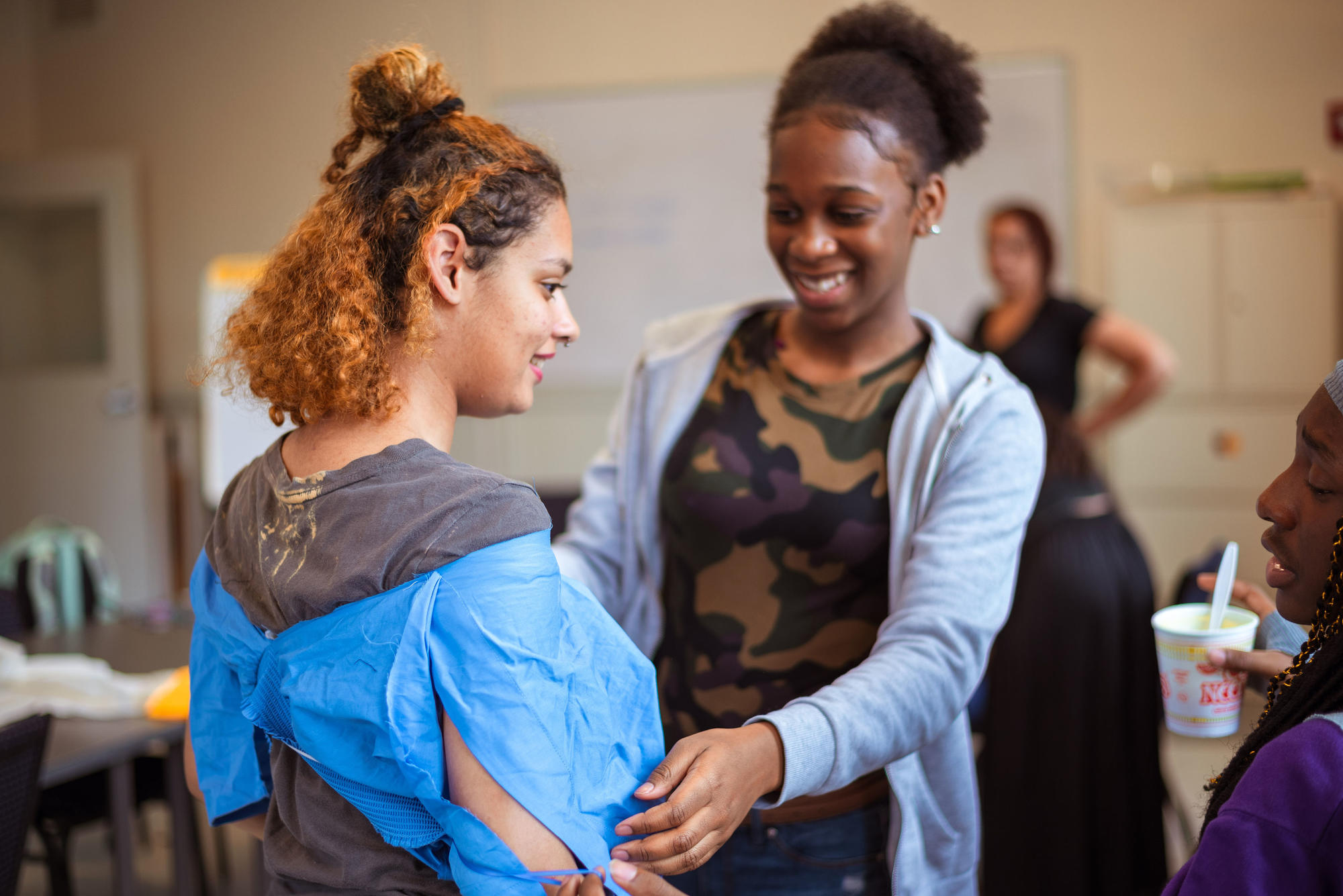 Two Hyde Square Task Force students work together to check the fit of their garments. Photo by Faizal Westcott, June 2019.