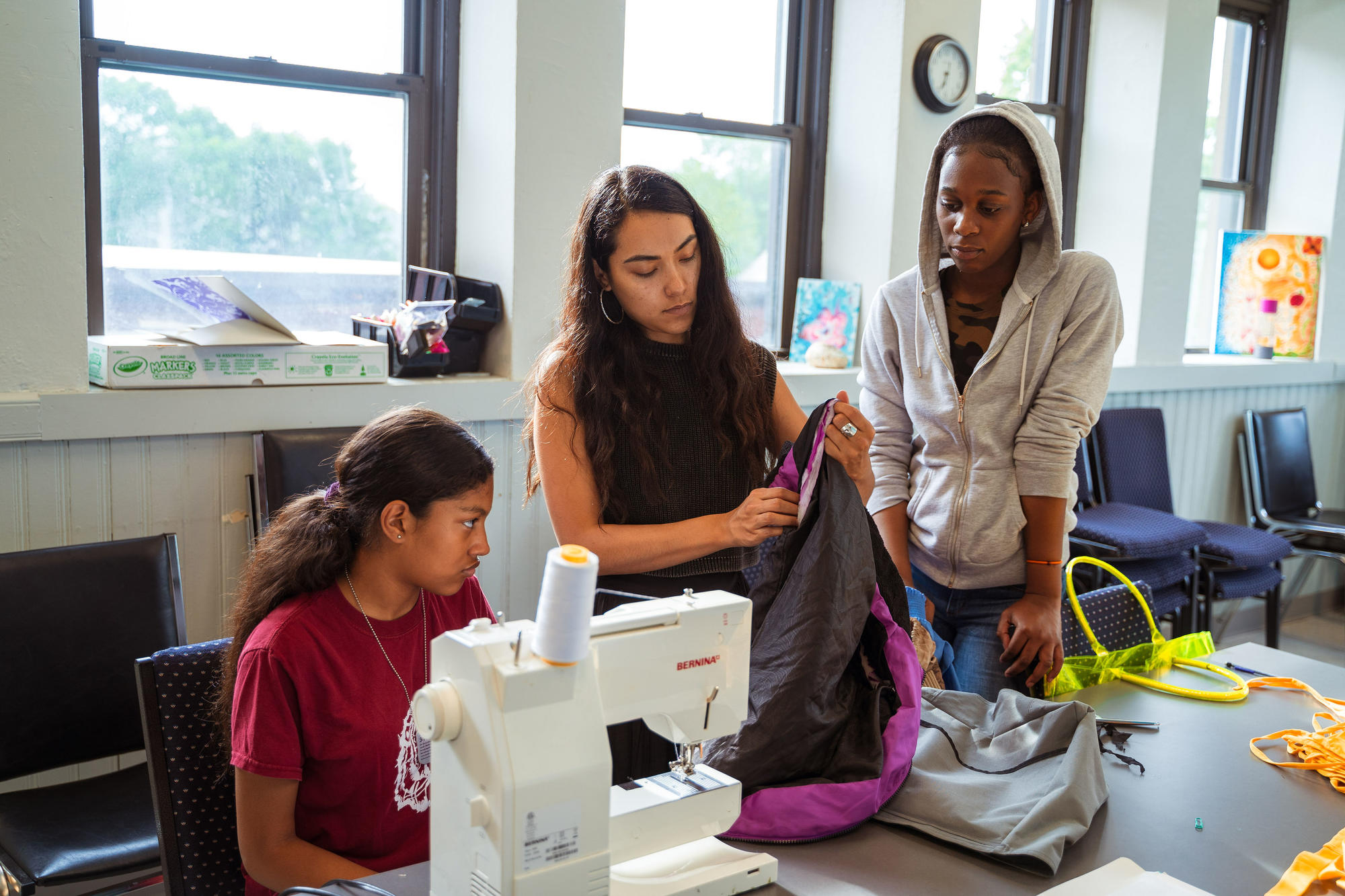 Nathalia JMag helps two Hyde Square Task Force Students with their sewing project.