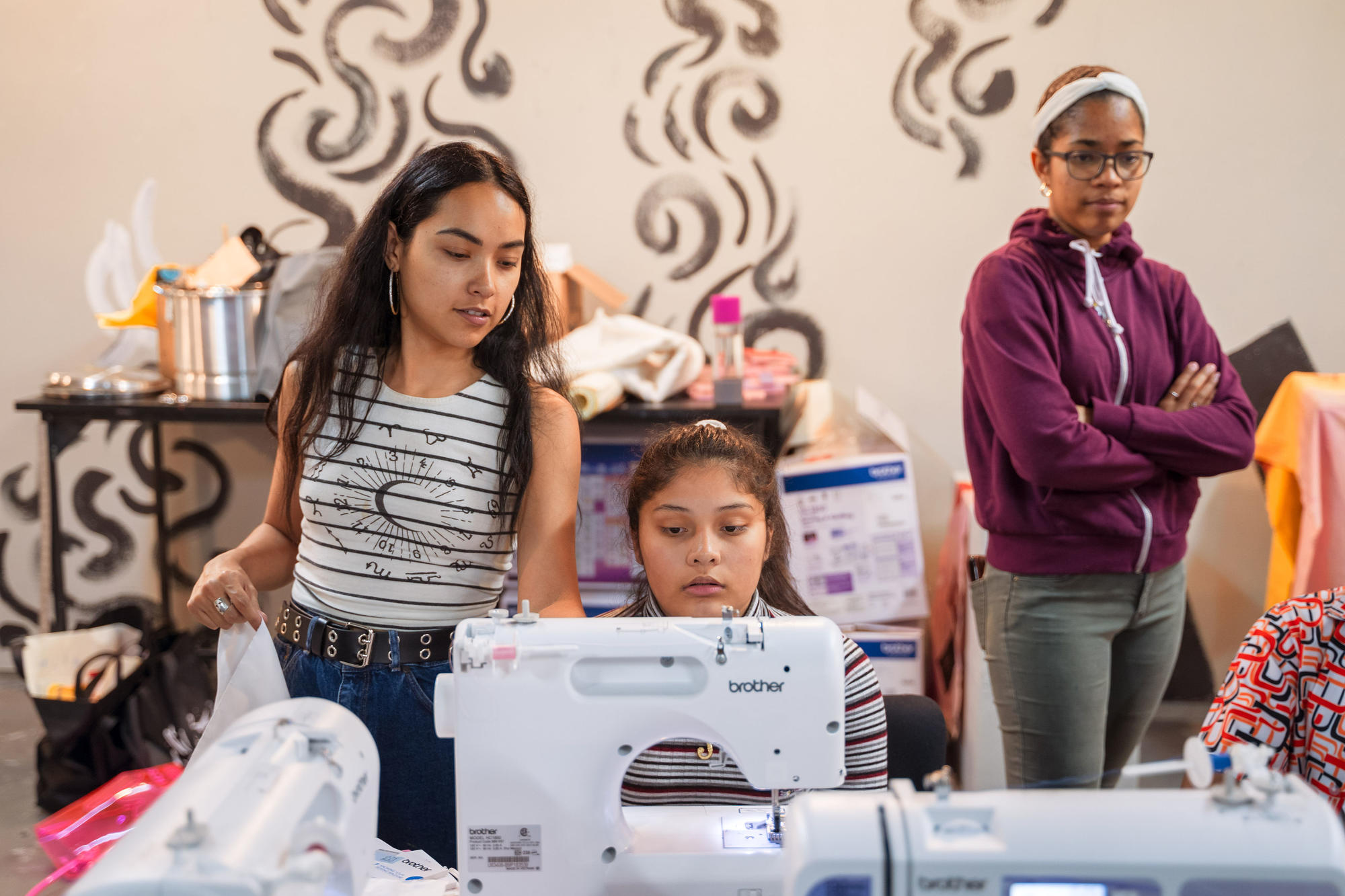 Nathalia JMag teaches Urbano Project students how to use a sewing machine.