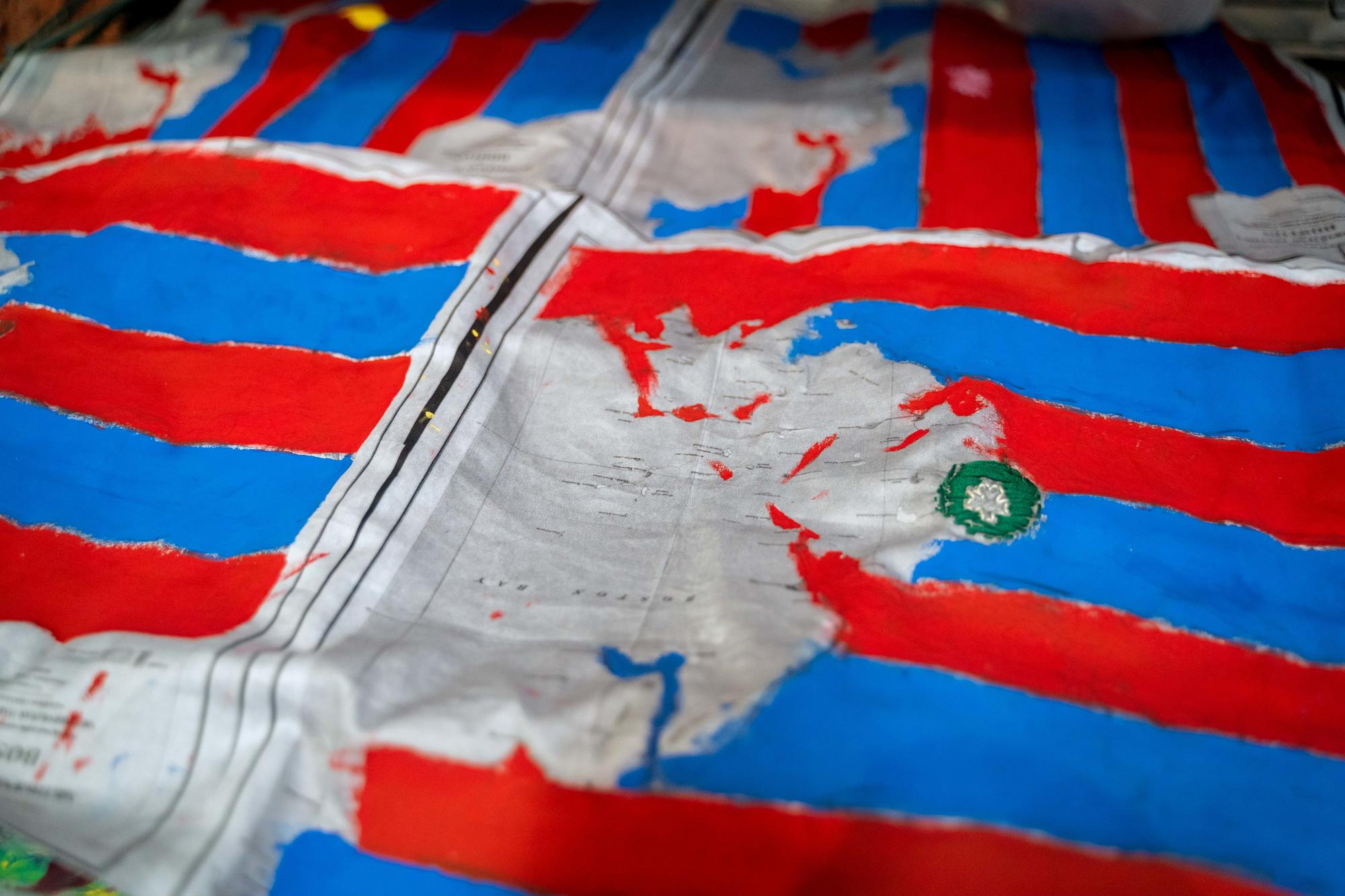 A close-up shot of a map-inspired textile with red and blue stripes obscuring the map beneath it, created by Urbano Project students.