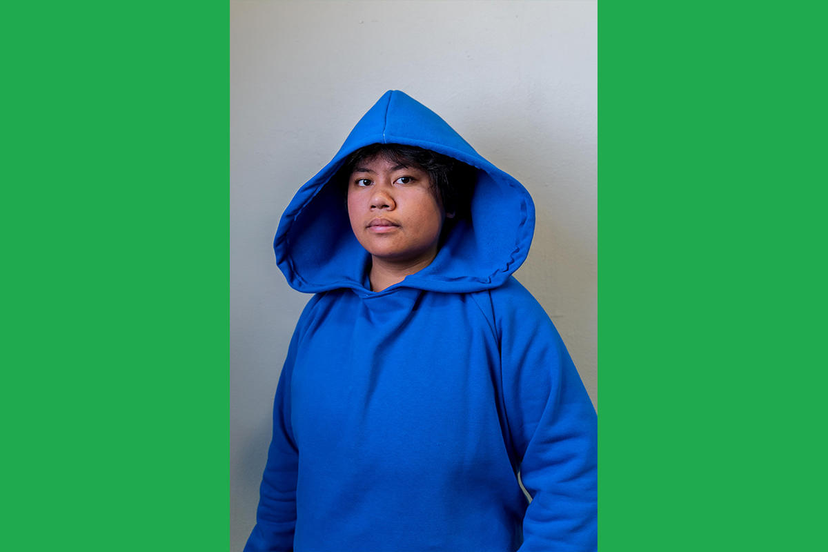 An Urbano Project student shows off their finished Map This garment: a royal blue hoodie with a wide, dramatic hood.