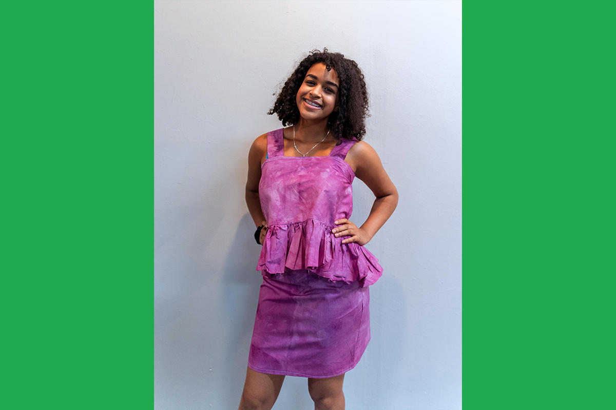 An Urbano Project student shows off their finished Map This garment: a tie-dyed pink top-and-skirt set. The top has a large ruffle at the waist.