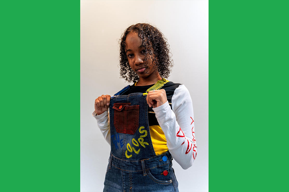 """An Urbano Project student shows off their finished Map This garment: a pair of denim overalls with painted-over buttons and the word """"colors"""" painted on the bib."""