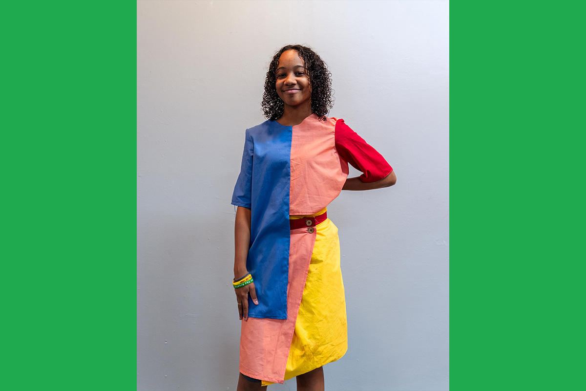 An Urbano Project student shows off their finished Map This garment: a colorblocked top-and-skirt set in bold primary colors..
