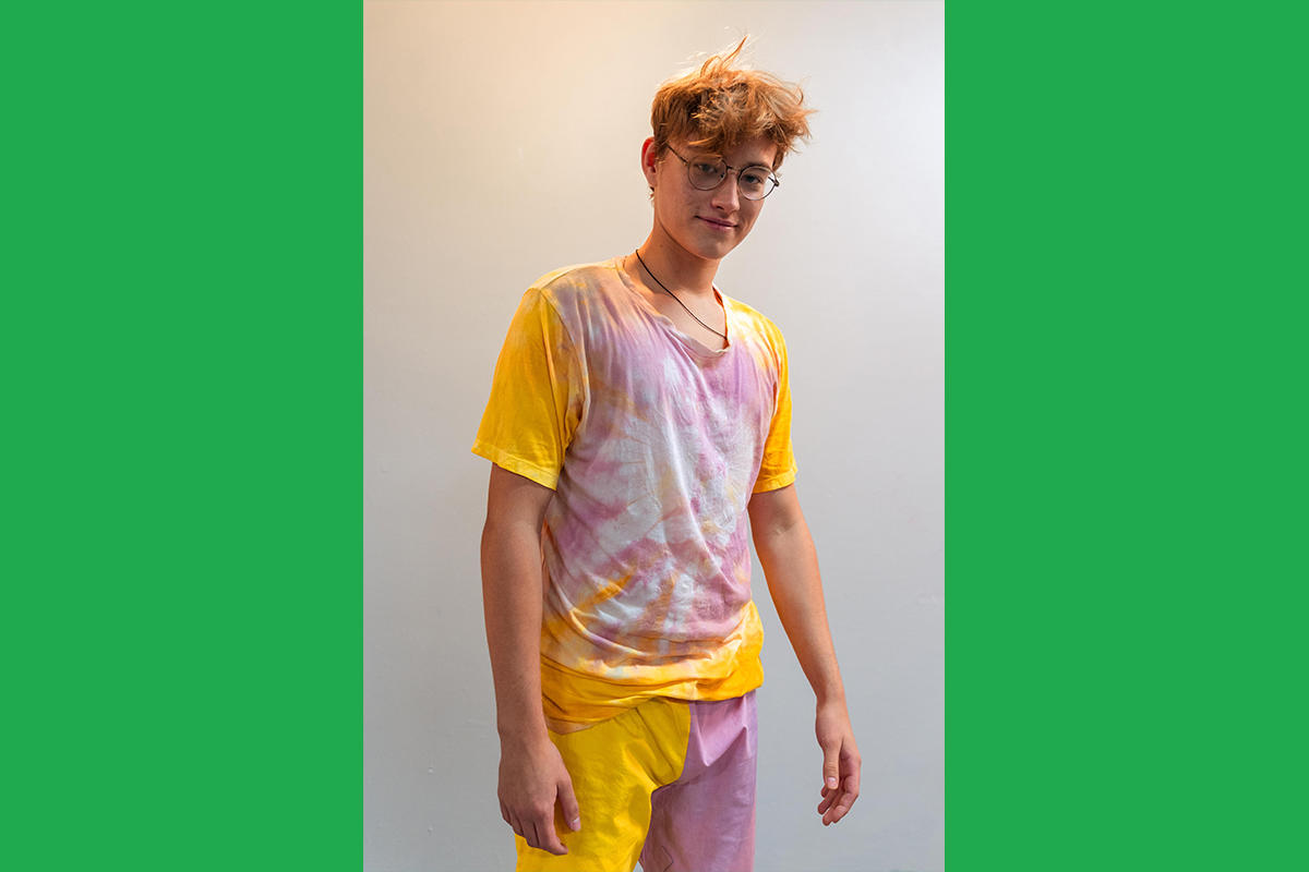 An Urbano Project student shows off their finished Map This garment: a yellow and pink tie-dyed T-shirt and colorblocked yellow and pink shorts.
