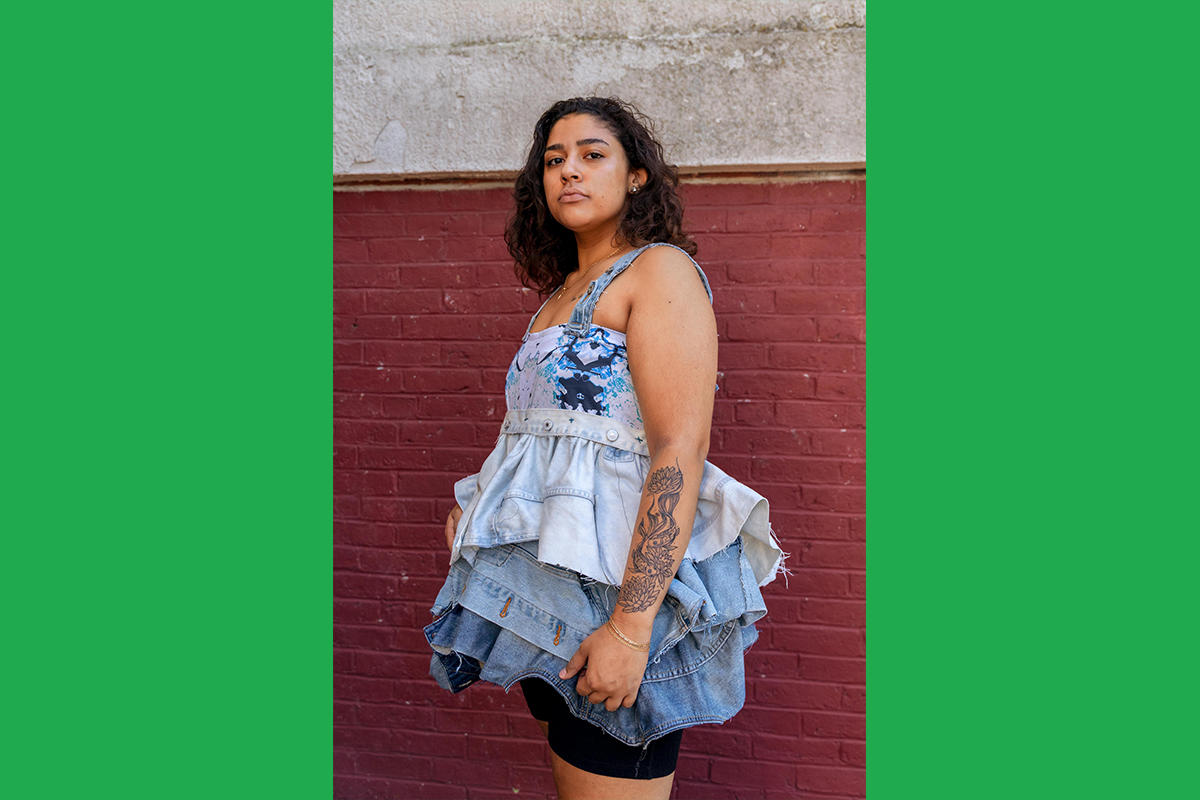 An Urbano Project student shows off their finished Map This garment: a top with large ruffles made of recycled denim in various washes, grading from light wash to medium.